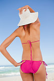 Back view of an attractive teenager in beachwear holding her str