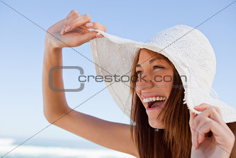 Young attractive woman screaming of joy in front of the sea