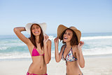 Happy young women standing on the beach side by side