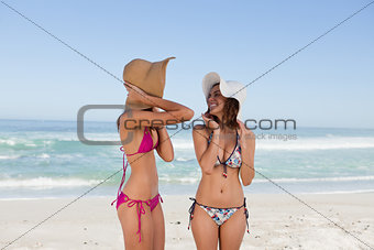 Attractive teenagers standing in front of the sea in beachwear