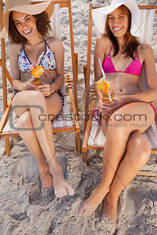 Young women laughing in deck chairs while holding fruit cocktail