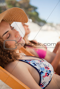 Beautiful woman napping on the beach on a deck chair