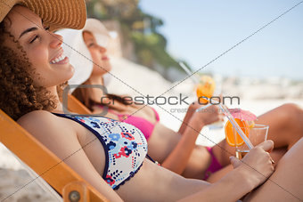Smiling young woman sitting in a deck chair while holding her co
