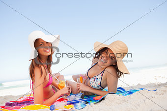 Young smiling women lying on beach towels while looking at the c