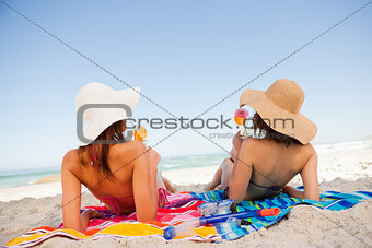 Back view of beautiful women sunbathing while sipping cocktails