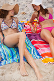 Young women lying on beach towels with cocktails while looking a