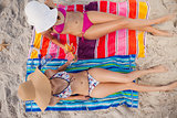 Overhead view of two young women tanning in the sun on the beach