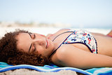 Side view of an attractive woman napping on the beach while turn