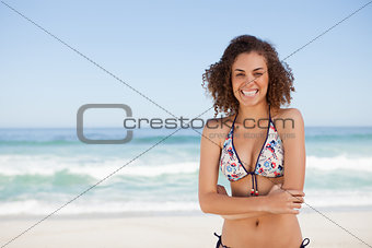 Young smiling woman standing in front of the sea with arms cross