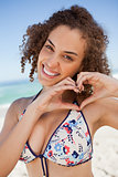Smiling young woman making a heart with her hands