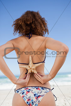 Young woman in swimsuit holding a starfish on her back