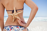 Young woman holding a starfish on her back with one hand