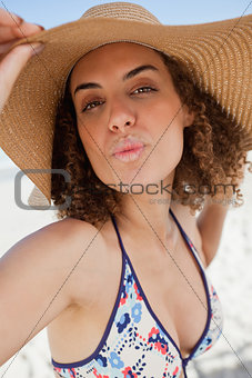 Young woman puckering her lips while holding her hat brim