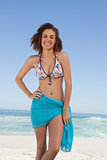 Smiling young woman wearing a blue sarong in front of the sea