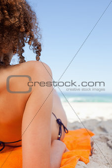 Back view of a young woman lying on her orange beach towel