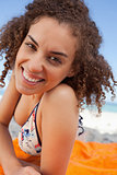 Young smiling woman lying down on a beach towel while staring at