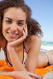 Young pretty woman lying on the beach with her hand on her cheek