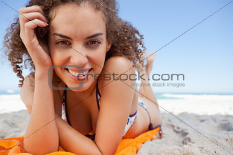 Young woman lying down while showing a great smile with her hand