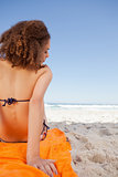 Rear view of a young woman sitting on a beach towel