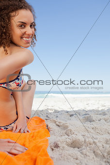 Young woman turning her head back while sitting on the beach