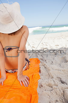 Rear view of a woman sunbathing while sitting on a beach towel