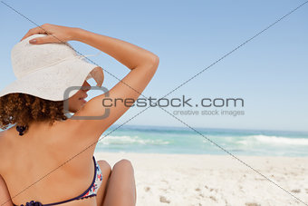 Young woman sitting on a beach towel while holding her hat
