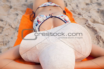 Relaxed young woman lying on her beach towel