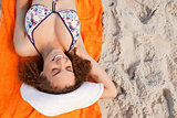 Overhead view of a smiling young woman lying on her beach towel