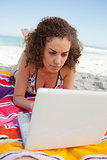 Young woman lying on her beach towel while using a laptop