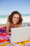 Young smiling woman typing on her laptop while lying on the beac