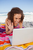 Young woman waving her hand in front of her laptop while lying o