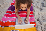 Overhead view of a young woman using her laptop on her beach tow