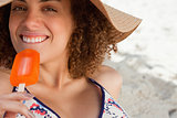 Young attractive woman going to eat an orange ice lolly on the b