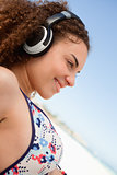 Beautiful young woman in bikini listening to music on the beach