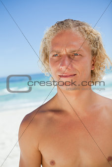 Serious blonde man looking towards the side while standing on th