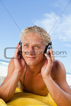 Smiling young man lying on his yellow beach towel while listenin