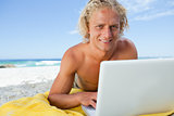 Smiling blonde man lying on the beach while using his laptop