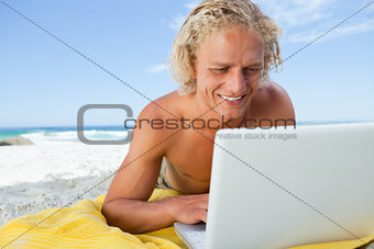 Smiling blonde man looking at his laptop while lying on the beac