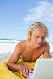 Blonde man lying on the beach while using his laptop in a very c