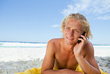 Young blonde man lying on the beach while talking on the phone