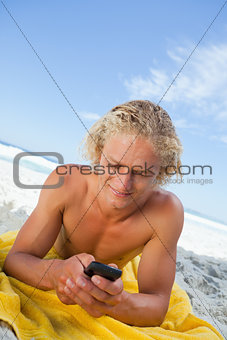 Blonde man lying on his beach towel while sending a text