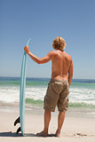 Young blonde man holding his surfboard in front of the ocean