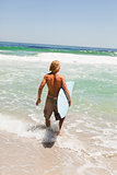 Young blonde man holding his surfboard while walking in the wate