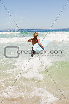 Blonde man running fast in the water while holding his surfboard