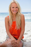 Young smiling blonde woman sitting on the beach
