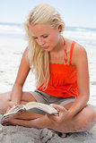 Young blonde woman sitting cross-legged while reading a book
