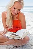 Young blonde woman reading a book while sitting cross-legged on