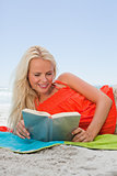 Young smiling woman lying on her beach towel while reading a book