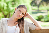 Thoughtful woman sitting on a park bench