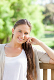 Smiling woman sitting on a bench in the park